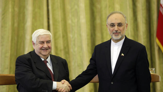 Syrian Foreign Minister Walid al-Moallem, left, and his Iranian counterpart Ali Akbar Salehi, shake hands, at the conclusion of their press conference, in Tehran, Iran, Saturday, March 2, 2013. The Syrian and Iranian foreign ministers on Saturday accused the United States of double standards over the Obama administration's decision to provide aid to rebels fighting to topple President Bashar Assad, saying this will only prolong the conflict. (AP Photo/Vahid Salemi)