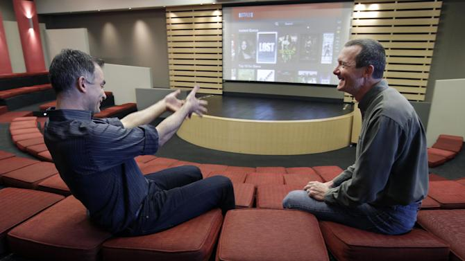 In this March 20, 2012, photo, Netflix executives John Ciancutti, left, and Neil Hunt talk inside a movie theater at the Netflix headquarters in Los Gatos, Calif. A big part of Netflix's future rides on how much Ciancutti and about 150 engineers can improve the software that draws up lists of TV shows and movies that might appeal to each of the video-subscription service's 26 million customers. Netflix has spent 13 years learning viewers' disparate tastes so it can point out movies they might enjoy. (AP Photo/Paul Sakuma)