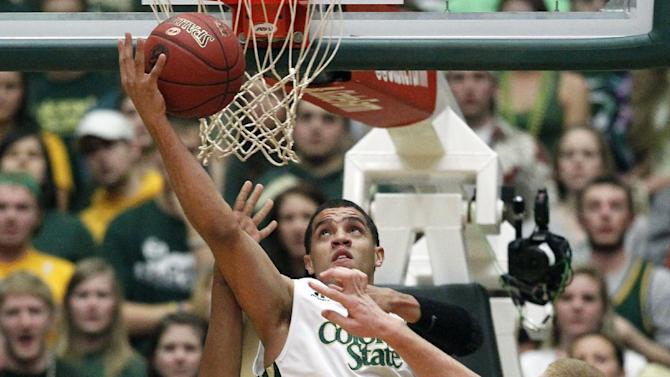 Colorado State guard Daniel Bejarano, center, tries to make a reverse layup between New Mexico forward Nick Banyard, left, and center Alex Kirk in the first half of an NCAA basketball game in Fort Collins, Colo., on Saturday, Feb. 23, 2013. (AP Photo/David Zalubowski)