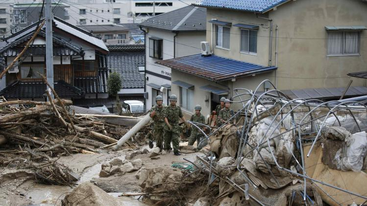 JSDF soldiers search for survivors as a site where a landslide swept through a residential area at Asaminami ward in Hiroshima