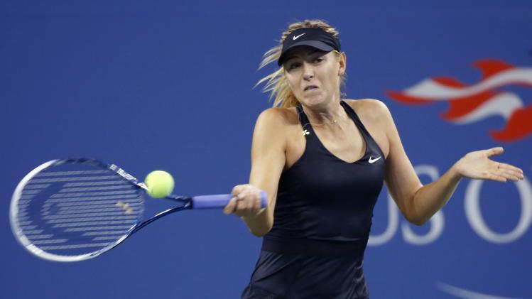 Sharapova of Russia returns a shot to Lisicki of Germany during their women's singles match at the U.S. Open tennis tournament in New York