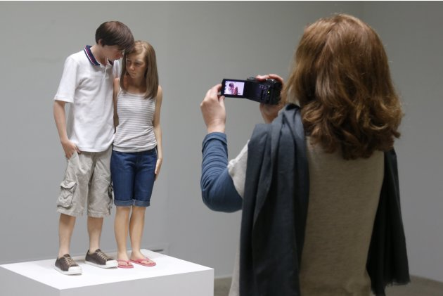 "A visitor shoots a sculpture entitled ""Young Couple, 2013"" by artist Ron Mueck during his exhibition at the Fondation Cartier pour l'art contemporain in Paris"