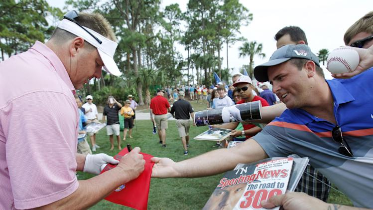 Former Major League Baseball pitcher Roger Clemens, left, signs autographs after playing in the celebrity group in the Pro-Am round of the Honda Classic golf tournament on Wednesday, Feb. 26, 2014, in Palm Beach Gardens, Fla. (AP Photo/Wilfredo Lee)