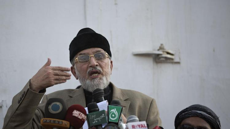 Anti-government cleric Tahir-ul-Qadri, gestures while delivering a speech to his supporters, during a protest in front of the Parliament building in Islamabad, Pakistan, Wednesday, Aug. 20, 2014. Pakistani lawmakers met Wednesday as tens of thousands of protesters thronged outside the assembly calling for the resignation of Prime Minister Nawaz Sharif over alleged voting fraud. (AP Photo/Muhammed Muheisen)