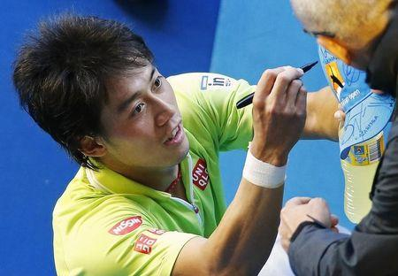 Nishikori of Japan signs autographs after defeating Ferrer of Spain in their men's singles fourth round match at the Australian Open 2015 tennis tournament in Melbourne