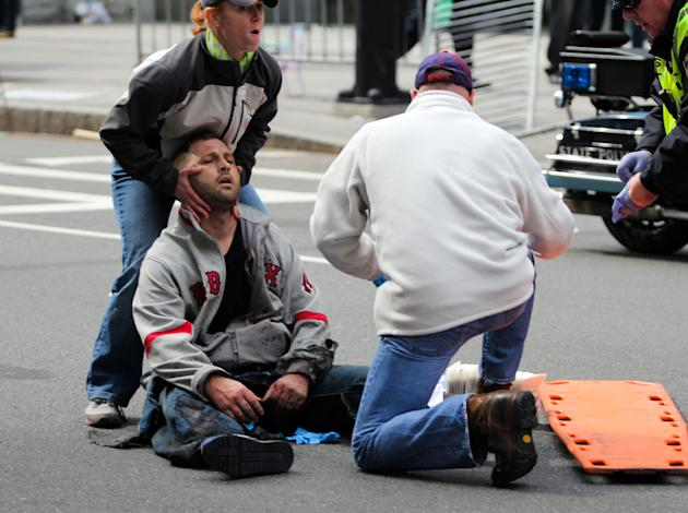In this photo provided by The Daily Free Press and Kenshin Okubo, people assist an injured after an explosion at the 2013 Boston Marathon in Boston, Monday, April 15, 2013. Two explosions shattered th