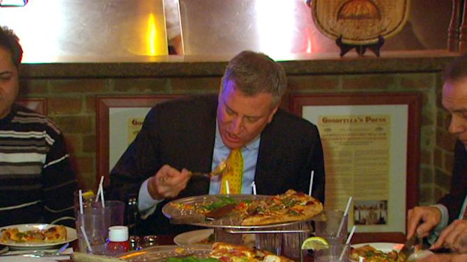 In this image taken from video and provided by New York City Hall, New York Mayor Bill de Blasio eats pizza with a fork at Goodfellas Pizza in the Staten Island borough of New York, Friday, Jan. 10, 2014. That's a no-no for most New Yorkers, who are very opinionated when it comes to proper pizza-eating technique. Many advocate using their hands to hold the slice, folding it like a taco and then taking a bite. (AP Photo/New York City Hall)