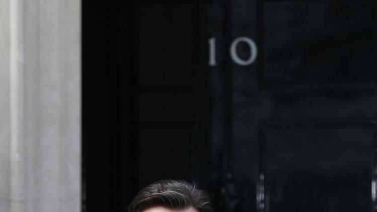 British Prime Minister David Cameron steps  out from 10 Downing Street, in London, Monday, April 8, 2013,  to pay tribute to former British Prime Minister Margaret Thatcher who died from a stroke,  at the age of 87. Thatcher's spokesman, Tim Bell, said the former prime minister died from a stroke Monday morning at the Ritz hotel in London.  (AP Photo/Sang Tan)