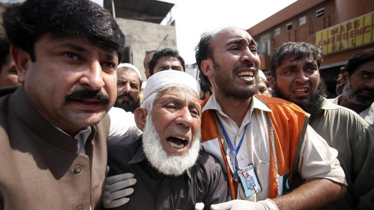 Man cries over the death of his son, who was killed in a bomb blast, at a hospital in Peshawar
