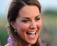 Catherine, the Duchess of Cambridge, laughs as she and her husband Britain's Prince William speak to dignitaries upon their arrival in Honiara on September 16. Britain's Prince William and wife Catherine were greeted by huge crowds as they landed in the lush, steamy Solomon Islands on Sunday, while a row raged in Europe about topless photos of the Duchess