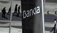Pedestrians are reflected in the Bankia headquarters building in Madrid