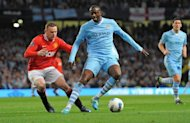 Manchester City&#39;s Ivorian midfielder Yaya Toure shields the ball from Manchester United&#39;s Wayne Rooney during a Premier League match in Manchester, north-west England, on April 30, 2012. Ivory Coast is in a strong position to capture the CAF Footballer of the Year award on Thursday, with two of its stars, Toure and Didier Drogba, Drogba, nominated against an up-and-coming midfielder from Cameroon