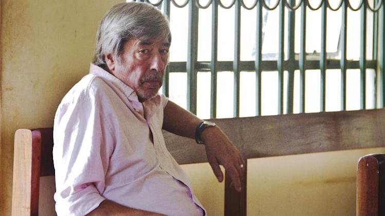 "Retired Briton Bernard Randall poses at the Entebbe Chief Magistrates Court on December 4, 2013 where he is facing charges of ""trafficking obscene publications"" after police found private pictures of him having sex with another man"