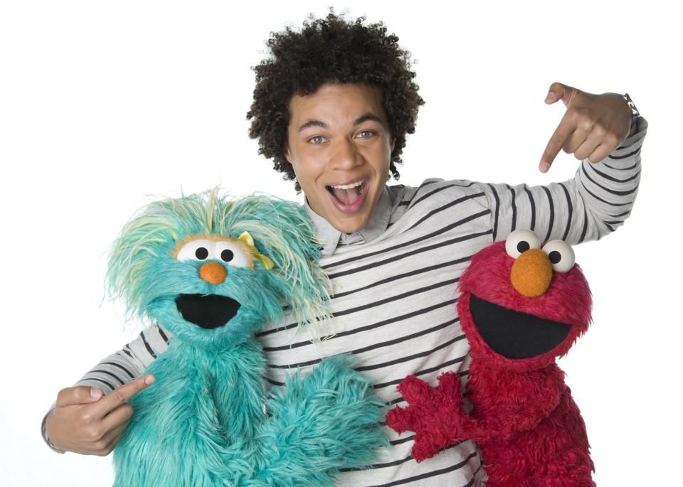 "This April 2013 photo released by Sesame Workshop shows  Puerto Rican actor Ismael Cruz Cordova, 26, of ""Sesame Street,"" posing with muppets Rosita, left, and Elmo in New York.  Cruz plays Mando, a young Latino writer who interacts with the puppets and also loves technology. (AP Photo/Sesame Workshop, Gil Vaknin)"