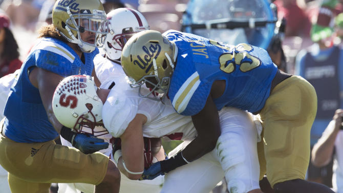 Stanford's running back Christian McCaffrey (27) gets wrapped up by UCLA's linebacker Eric Kendricks (6) and UCLA's linebacker Myles Jack (30) during the first half of an NCAA college football game, Friday, Nov. 28, 2014, in Pasadena, Calif. Stanford won 31-10. (AP Pho to/The Orange County Register, Michael Goulding)   MAGS OUT; LOS ANGELES TIMES OUT