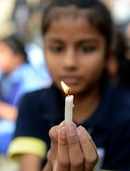 A schoolgirl holds a candle during a rally in Ahmedabad, India, on December 29, 2012. The body of a gang-rape victim arrived back in New Delhi on Sunday after her death from sickening injuries in a Singapore hospital as India was engulfed by a mass outpouring of grief and anger
