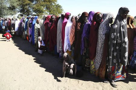 Women who have fled violence in Nigeria queue for food at a refugee welcoming center in Ngouboua