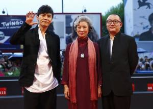 """Director Wang Xiaoshuai poses with cast members Qin Hao and Lu Zhong during the red carpet for the movie """"Chuangru zhe"""" (Red amnesia) at the 71st Venice Film Festival"""