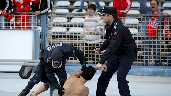 A Benfica supporter is blocked by policemen during the celebration of Benfica's Jonas Oliveira's goal during their Portuguese Premier League soccer match against Belenenses at Restelo stadium in Lisbon