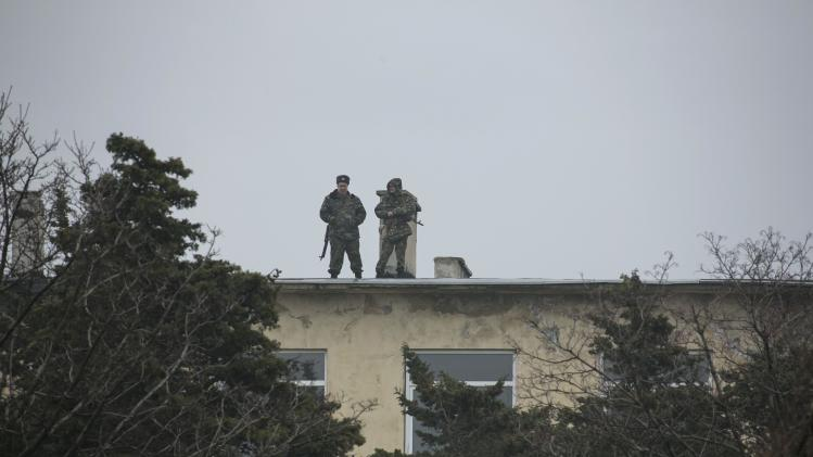 Ukrainian servicemen walk on the roof of their base as uniformed men believed to be Russian servicemen stand guard near Sevastopol