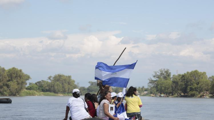 "Women from ""Caravana de Madres Centroamericanas"" displays photos of missing migrants and a Salvadorian flag as they ride a raft to cross to Guatemala from the Suchiate river in the border of Ciudad Hidalgo"