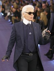 German fashion designer Karl Lagerfeld acknowledges applause at the end of the presentation for Chanel, after his Women's Spring Summer 2012 Haute Couture fashion collection presented in Paris, Tuesday, Jan. 24, 2012. (AP Photo/ Jacques Brinon)