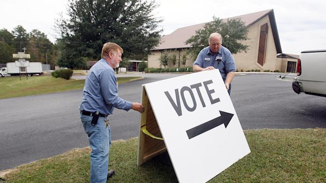 """Shawn Lake, left, and Anthony Beck, Tuscaloosa County maintenance department employees, set up a """"Vote"""" sign in front of Flatwoods Baptist Church in Northport, Ala., Monday, Nov. 5, 2012. The church is just one of 54 different polling places located throughout Tuscaloosa County. The men traveled around the county setting up polls in advance of Tuesday's elections. The majority of the locations have one or two polling machines while others have a maximum of up to four. Polls are open Tuesday from 7 AM to 7 PM. (AP Photo/Tuscaloosa News, Michelle Lepianka Carter)"""