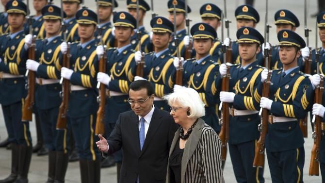 Iceland's Prime Minister Johanna Sigurdardottir, right, is shown the way by Chinese Premier Li Keqiang after inspecting a guard of honor during a welcome ceremony outside the Great Hall of the People in Beijing Monday, April 15, 2013. (AP Photo/Andy Wong)