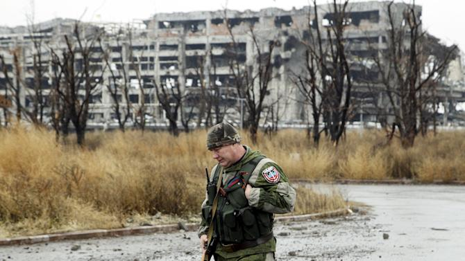 A member of the self-proclaimed Donetsk People's Republic forces walks along a road near buildings that were destroyed during battles with the Ukrainian armed forces, at the Donetsk airport in Ukraine