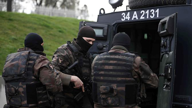 Members of special security forces prepare outside the main courthouse in Istanbul, Turkey, Tuesday, March 31, 2015. Turkish news agencies say that members of a banned leftist group have taken a chief prosecutor hostage in his office inside the courthouse. State-run Anadolu Agency and state television, TRT, identified the prosecutor as Mehmet Selim Kiraz. He is the prosecutor investigating the death of a teenager who was hit by a police gas canister fired during nationwide anti-government protests in 2013.(AP Photo/Emrah Gurel)