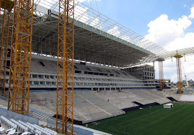 A workman walks through a grandstand in the Arena Sao Paulo stadium as construction continues in Sao Paulo