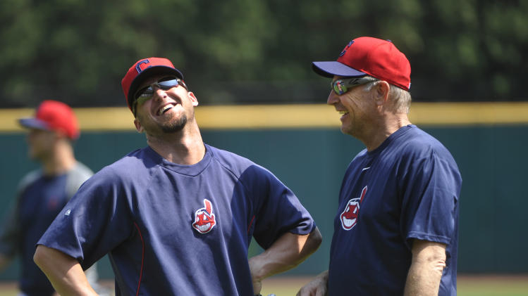 """Actor Kevin Costner, right, gets a laugh from Cleveland Indians outfielder Ryan Rayburn before Costner takes warm-ups with the Indians before their game against the Minnesota Twins, in Cleveland, Sunday, June 23, 2013. Costner has been in Cleveland filming scenes for the movie """"Draft Day""""(AP Photo/Phil Long)"""