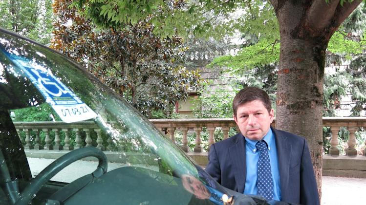 Portland, Ore., city commissioner Steve Novick stands next to a car in downtown that uses a disabled placard to park for free without a time limit on Thursday, Sept. 5, 2013, in Portland, Ore. Those cars stay all day long, costing the city meter revenue while reducing the turnover that shop owners like to see. Portland officials are now looking to charge disabled people who are not in wheelchairs for parking. (AP Photo/Nigel Duara)