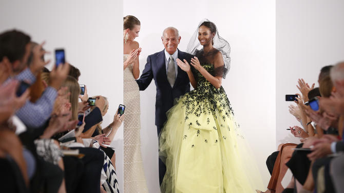 Designer Oscar de la Renta, center, greets the audience after his Spring 2014 collection was modeled during Fashion Week in New York, Tuesday, Sept. 10, 2013. (AP Photo/John Minchillo)
