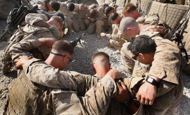 U.S. Marines pray before heading out on patrol in Kajaki, Afghanistan, in 2010.