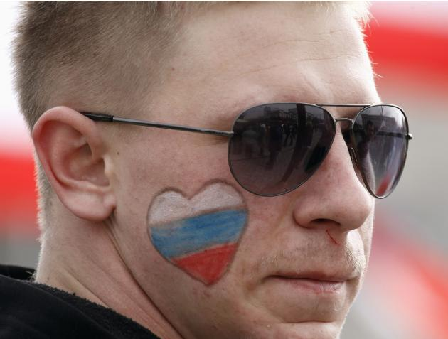 A pro-Russian supporter with a painted Russian flag on his face attends a rally in Simferopol
