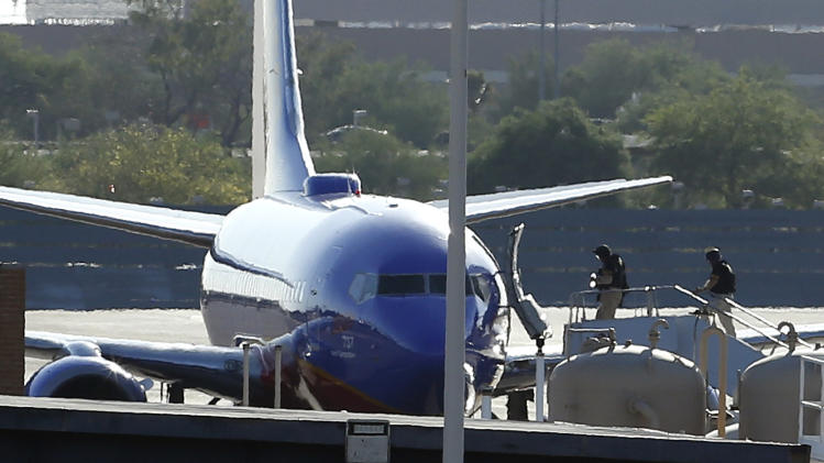 "Members of the bomb squad walk onto a Southwest Airlines plane on the ground at Phoenix Sky Harbor International Airport after the FBI says a ""telephonic bomb threat"" against a Southwest flight from Los Angeles to Texas led to the plane being diverted to Phoenix on Monday, June 10, 2013. Flight 2675 left Los Angeles International Airport at 2:12 p.m. and was heading to Austin before the threat was received by telephone. The plane landed safely at the Phoenix airport at about 3 p.m. (AP Photo/Ross D. Franklin)"