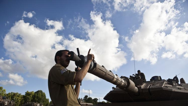 An Israeli soldier adjusts the barrel of a tank outside northern Gaza