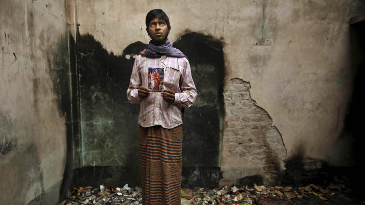 In this Friday, Dec. 21, 2012 photo,  Bangladeshi Saddam Hussein, 24, holds a photograph of his wife 20-year-old Mitu Begum, a sewing machine operator who died in the fire at Tazreen Fashions, in the garment district in Ashulia, near Dhaka, Bangladesh. When fire ravaged the Bangladeshi garment factory, killing 112 workers, dozens of their families did not even have a body to bury because their loved ones' remains were burned beyond recognition. Two months later, they have yet to receive any of the compensation they were promised - not even their relatives' last paychecks. (AP Photo/Kevin Frayer)