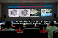 Chinese technicians at the Jiuquan Space Centre monitor the Shenzhou-9 spacecraft as it prepares to link with the Tiangong-1 module. A Chinese spacecraft has successfully completed the country's first manual docking in orbit, a milestone in an ambitious programme to build a space station by the end of the decade