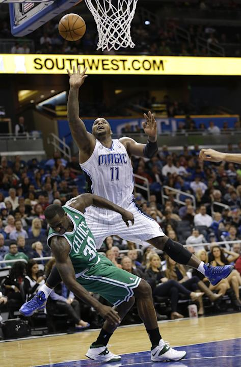 Orlando Magic's Glen Davis (11) makes a shot and draws a foul from Boston Celtics' Brandon Bass (30) during the second half of an NBA basketball game in Orlando, Fla., Sunday, Jan. 19, 2014. O