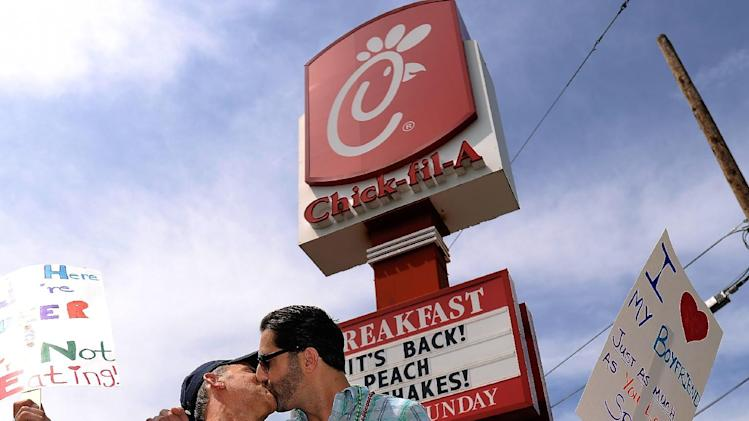 Jim Fortier, left, and Mark Toomajian, kiss as they join about two dozen members of gay rights groups and others protesting outside the Decatur, Ga., Chick-fil-A restaurant Friday, Aug. 3, 2012.  Gay rights activists plan kiss demonstrations at Chick-fil-A stores Friday, just days after the company set a sales record when customers flocked to the restaurants to show support for the fast-food chain owner's opposition to gay marriage. (AP Photo/David Tulis)