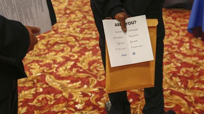 Man holds a pamphlet handed out by a recruiter while attending a job fair in New York