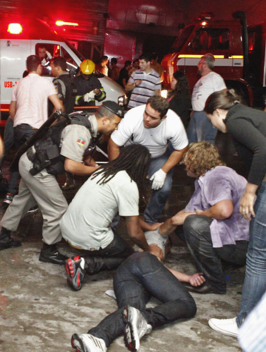 ALTERNATIVE CROP OF XSI103.- People help an injured man, victim of a fire in a club in Santa Maria city, Rio Grande do Sul state,  Brazil,  Sunday, Jan. 27,  2013.  According to police more than 200 d