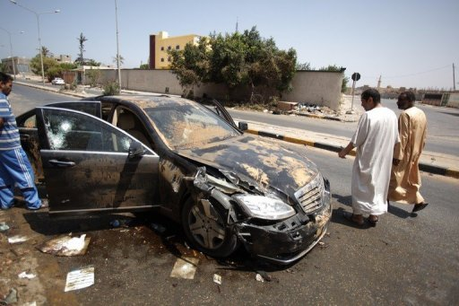 Libyans walks past the destroyed bullet proof car of Libyan former Prime Minister Baghdadi al-Mahmoudi in Tripoli in 2011. Tunisia's decision to extradite Libya's former prime minister Baghdadi al-Mahmoudi back to his home country is definitive, Prime Minister Hamadi Jebali said