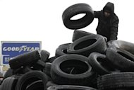 A Goodyear worker installs tyres symbolizing the 1,173 employees next to the Goodyear tyres factory in Amiens, February 26, 2013. REUTERS/Pascal Rossignol