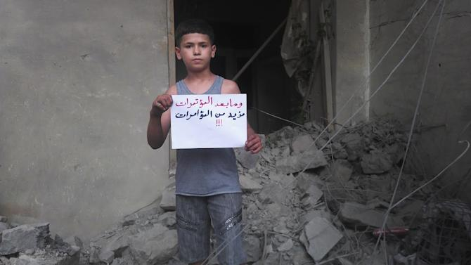 "In this citizen journalism image provided by Shaam News Network SNN, taken on Wednesday, July 11, 2012, a Syrian boy holds a poster with Arabic that reads, ""and what happens after press conferences, even more press conferences!"" in Homs, Syria. (AP Photo/Shaam News Network, SNN)THE ASSOCIATED PRESS IS UNABLE TO INDEPENDENTLY VERIFY THE AUTHENTICITY, CONTENT, LOCATION OR DATE OF THIS CITIZEN JOURNALIST IMAGE"