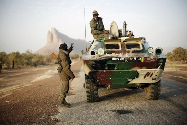 A convoy of Malian troops makes a stop to test some of their weapons near Hambori, northern Mali, on the road to Gao, Monday Feb. 4, 2013. French troops launched airstrikes on Islamic militant training camps and arms depots around Kidal and Tessalit in Mali&#39;s far north, defense officials said Sunday, as the first supply convoy of food, fuel and parts to eastern Mali headed across the country. (AP Photo/Jerome Delay)