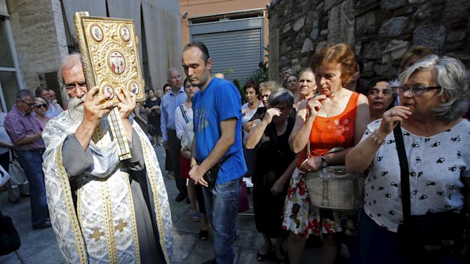 A Greek Orthodox priest holds a Holy Gospel during a celebration of a saint in a church in central Athens