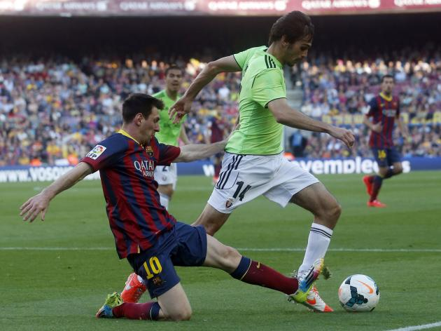 Barcelona's Lionel Messi fights for the ball against Osasuna's Alejandro Arribas during their Spanish first division soccer match at Camp Nou stadium in Barcelona